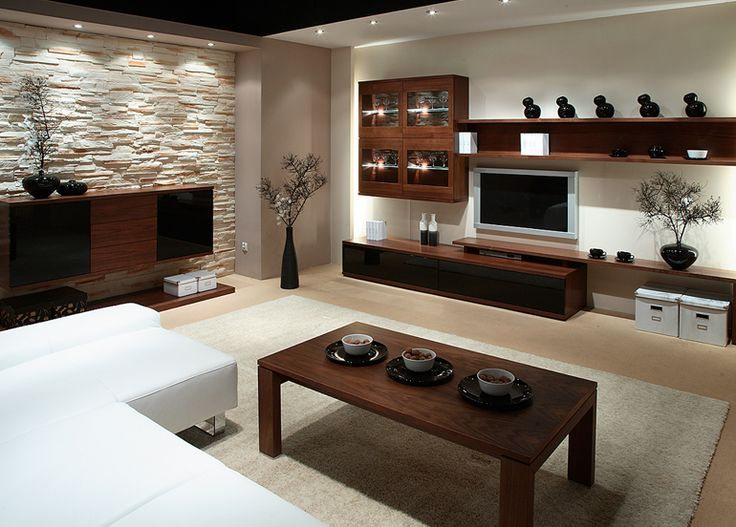 Il marrone rossiccio del ciliegio e le ante nero lucido del mobile soggiorno alleggeriti dalla parete in pietra bianca e dal divano bianco movimentano l'ambiente