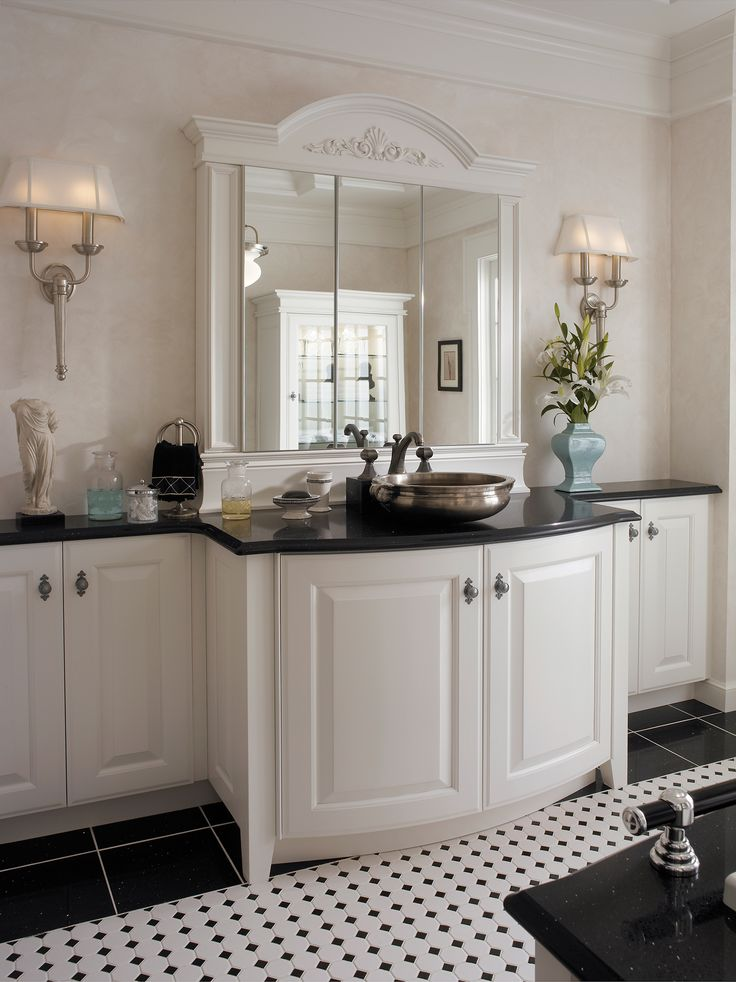 Classic elements including an eyebrow pediment enhance the formal English appeal of this bath.