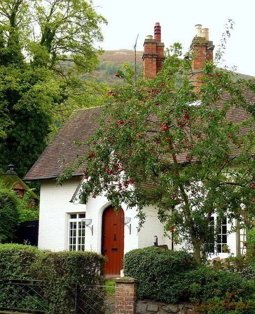 Red Arched Door In This Diminutive White Stucco Cottage