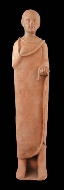 Grande statue votive. Elle représente un jeune garçon debout, vêtu de la toga enveloppante. Il a le bras droit ramené sur la poitrine et sa main gauche fermée est ornée d'une bague. Sa tête, au visage juvénile, présente une coiffure formée de mèches parallèles. Au sommet de la tête, un trou d'évent. Terre cuite beige. Art Étrusque, IIIe-IIe siècle av. J.-C. H_110 cm Etruscan terracotta votive statue of a youth. 3rd-2nd century B.C. 43,3 in. high