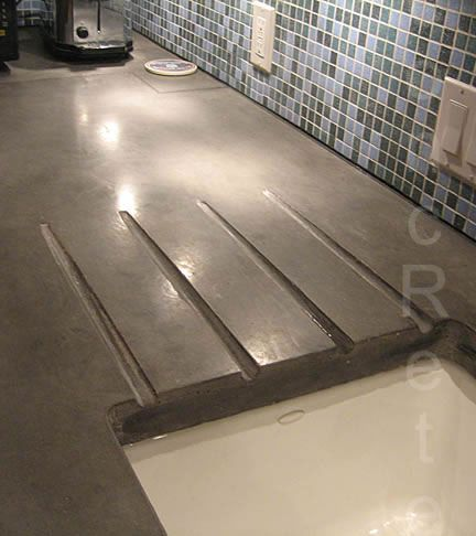 Concrete counter with built in drainage grooves.
