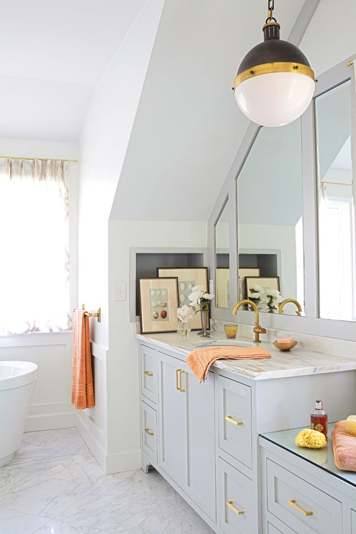 Bright bathroom with brass fixtures and neutral painted for Master bathroom fixtures
