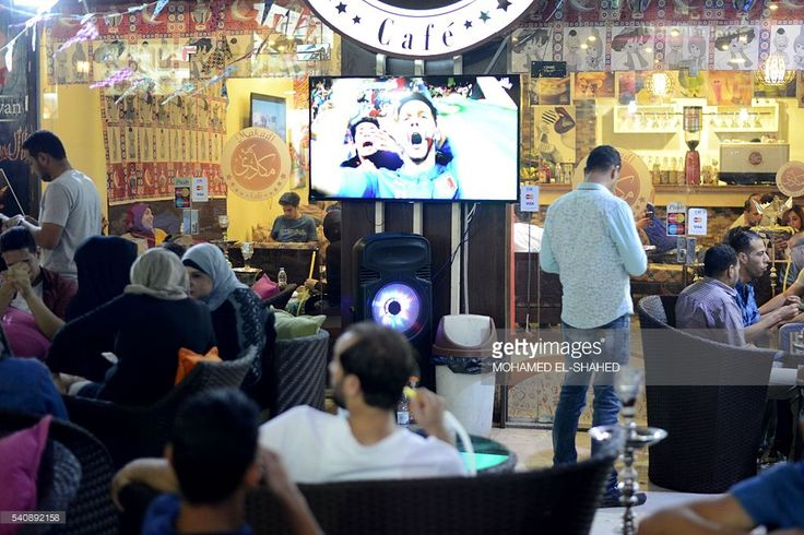 Egyptians watch the Euro 2016 group E football match between Belgium and Italy, taking place at the Parc Olympique Lyonnais stadium in the French city of Lyon, on June 13, 2016 at a café in the Egyptian capital Cairo. From Dubai to Tunis, Euro 2016 football fever is sweeping the Arab world, filling cafes and restaurants and overshadowing popular Ramadan soaps on television. HOWAYK
