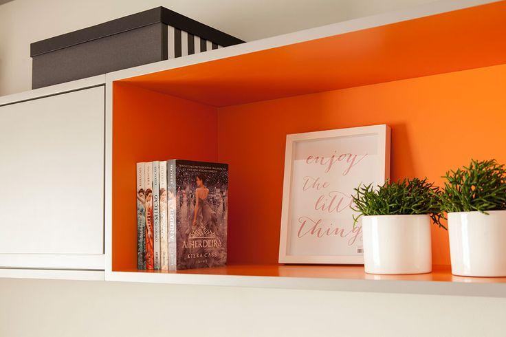 Decoração de apartamento com ambientes integrados e varanda. Detalhes da decoração do quarto de solteiro com nicho branco e laranja, livros, plantas na decoração, quadros.