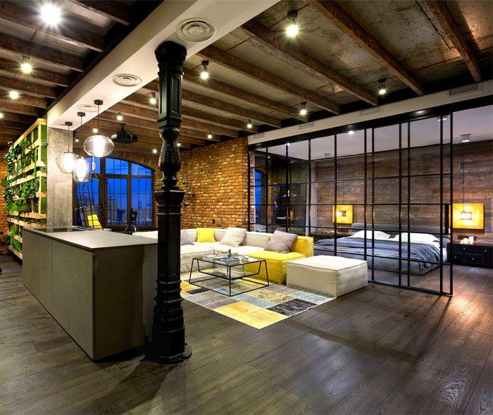 Le grand espace d'un loft aménagé et structuré grâce à une paroi vitrée et de grands canapés qui apportent des touches de couleur.
