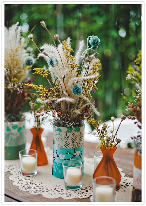 Decorated tin can, dried floral centerpieces and candles