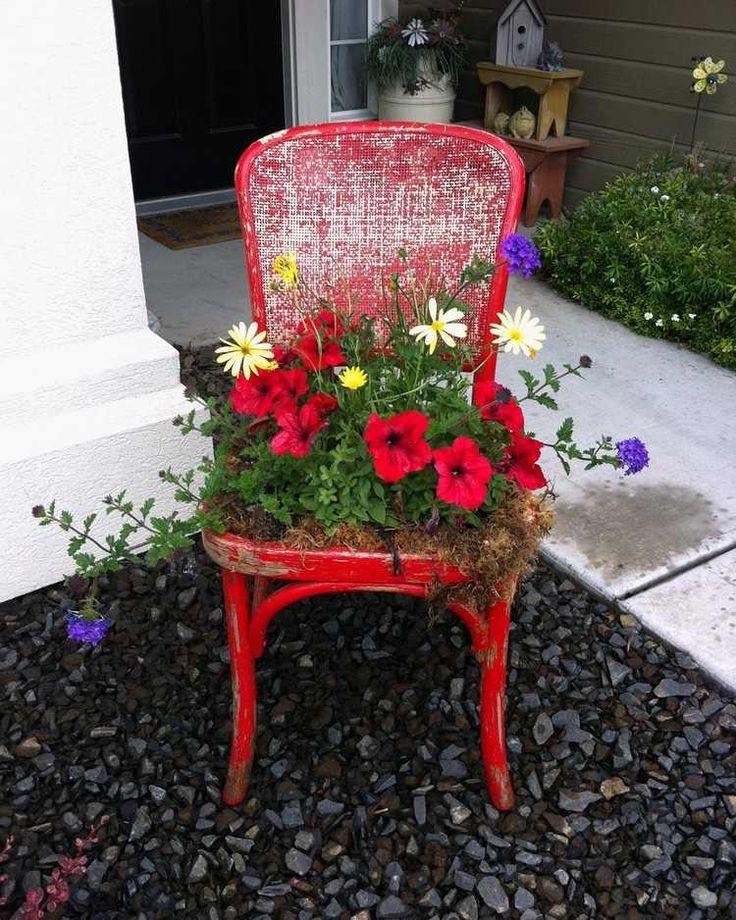 rot lackierter Stuhl mit Blumen bepflanzt