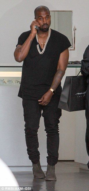 Simply stylish: Kanye headed out in a pair of straight leg black jeans with a V-neck black T-shirt which showed off his two gold chains - one simple dainty one and a giant impossible to miss one