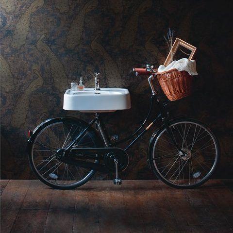 Rechthoekige wastafel gepositioneerd op een houten plateau die bevestigd is op een fiets. De wastafel is beschikbaar zonder gaten en met 1, 2 of 3 voorgeboorde gaten. Dit is belangrijk bij de keuze van de kraan die u er op wenst aan te sluiten.
