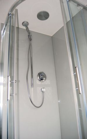 Photograph of Opticolour dove grey glass bath panels which have been drilled to accomodate shower attachments