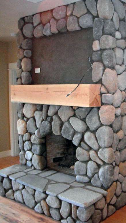 River rock real wood burning fireplace with space for TV above mantle.