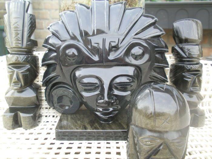 Drie Aztekenbeeldjes en een masker gemaakt van obsidiaan uit Mexico  Het betreft hier drie originele Aztekenbeeldjes en een masker gemaakt van obsidiaan uit Mexico.Deze beeldjes zijn meegenomen van vakantie in 1970 vanuit Mexico.Deze voorwerpen zijn vervaardigd door lokale kunstenaars.De Azteken waren een kunstzinnig indianenvolk. Zij geloofden in vele verschillende goden die aanwezig zouden zijn in elk levend ding. Deze beeldjes zijn gemaakt van obsidiaan naar oude voorbeelden zoals…