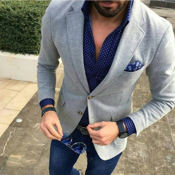 Choose a grey wool suit jacket and dark blue jeans for drinks after work.   Shop this look on Lookastic: https://lookastic.com/men/looks/grey-blazer-navy-long-sleeve-shirt-navy-jeans/20599   — Navy Polka Dot Long Sleeve Shirt  — Navy Paisley Pocket Square  — Grey Wool Blazer  — Navy Jeans