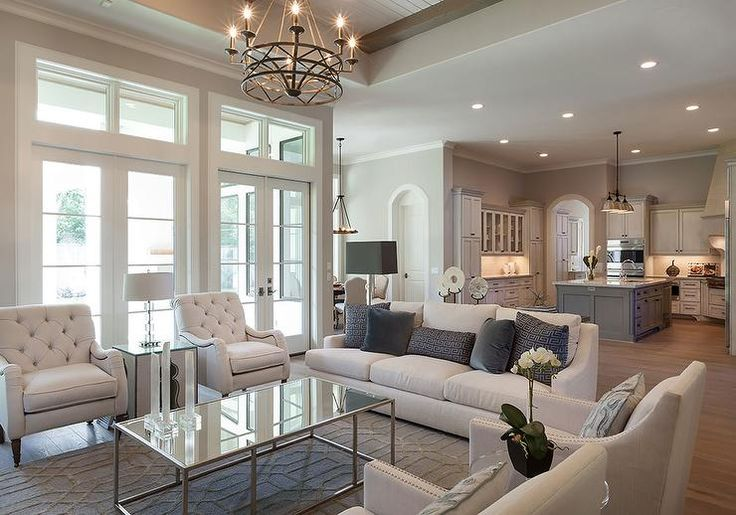 Lovely living room features a pair of ivory linen nailhead chairs facing a pair of ivory tufted chairs across from a rectangular mirrored coffee table alongside a white swoop arm sofa atop a blue trellis rug illuminated by an iron candelabra chandelier.