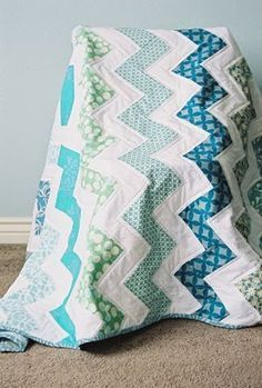 """zig zag quilt Need 7 quarter yards (not fat quarter) of solid and 7 of pattern 1/2 yard for binding 2.5 for backing Cut 1 solid fabric strip 3"""" wide and full length of fabric  Cut 1 pattern strip same and sew together. Cut this into 5.5"""" squares and piece into zig zag pattern."""