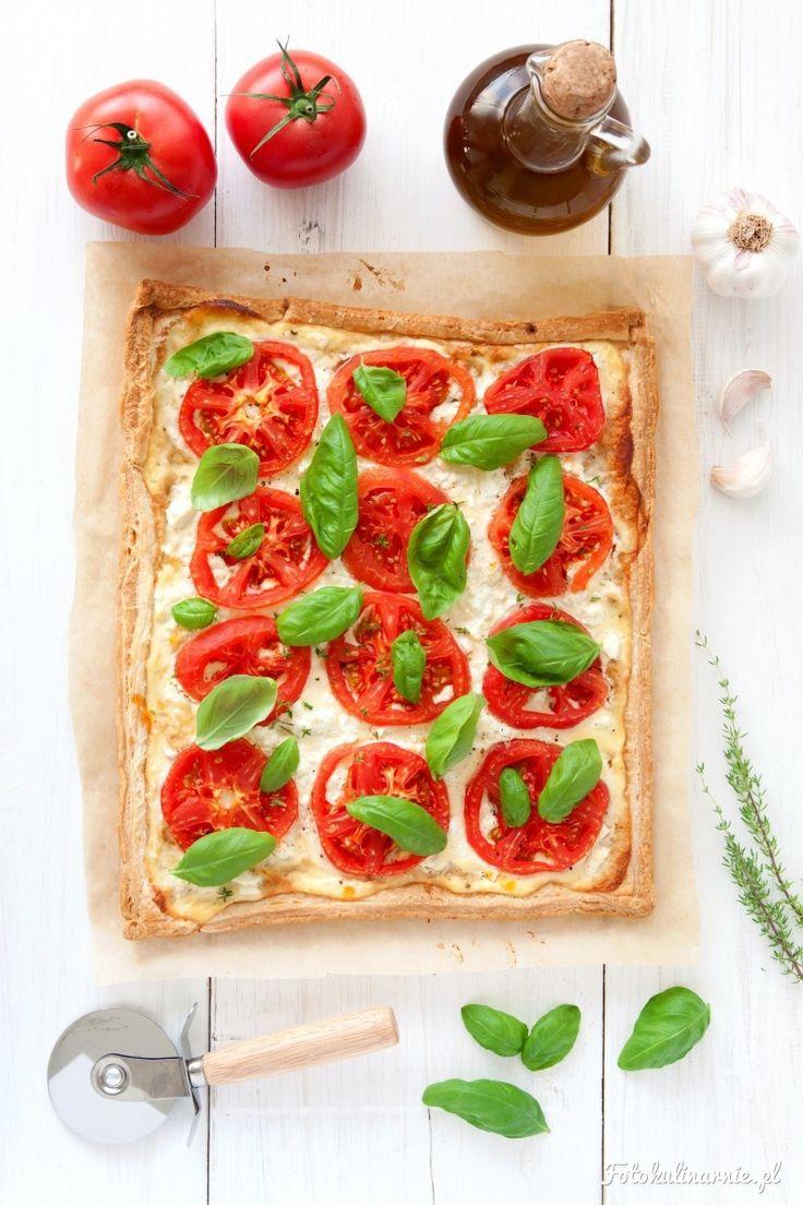 Kolorowa tarta z pomidorami i fetą, na cieście francuskim, posypana bazylią, to idealna przekąska albo też cały posiłek.