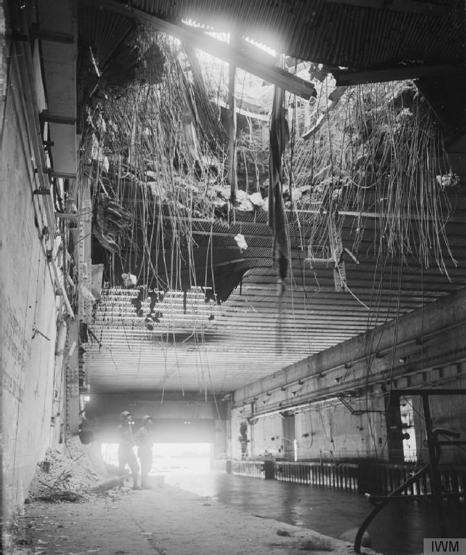 A forty-foot circle hole in the roof of a U-boat pen in Brest which had received a direct hit during the Allied bombardment. The capture of the deep water ports of Brittany did not greatly help the Allies, however, since the Germans had, as in Cherbourg, carried out thorough demolition of the port facilities before surrendering.