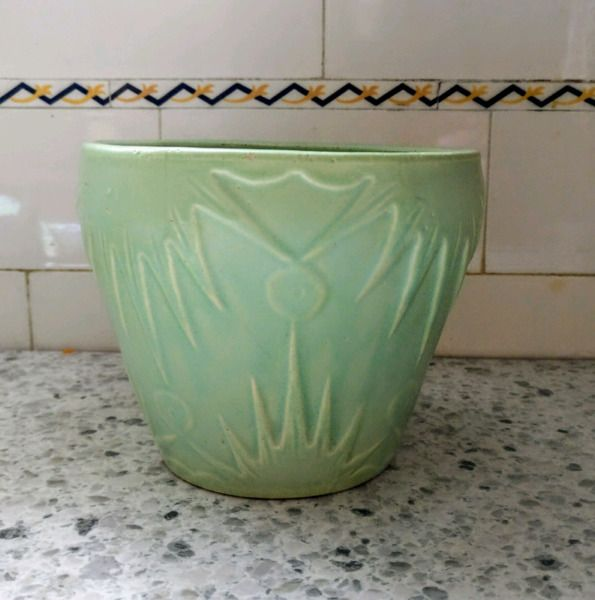 this petite jardiniere was manufactured in the 1930's by robinson ransbottom pottery co. also known as r.r.p. co. from roseville, ohio. the art deco sun moon design from the 1930's has a celadon green matte glaze. the planter does not appear to have been used. there are no chips cracks or crazing. the glaze pops and grit are from the original factory firing. the base is marked