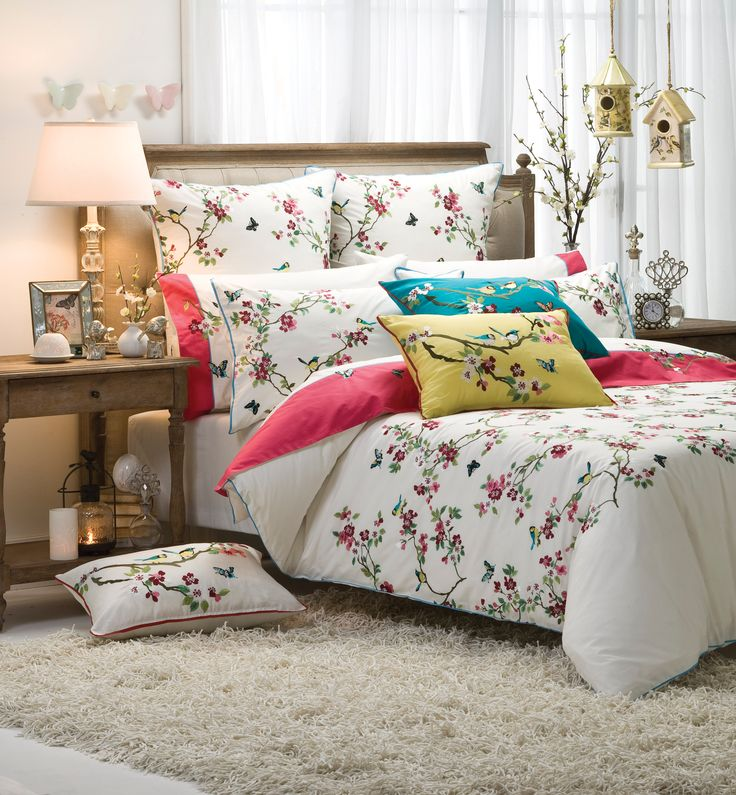 With an abundance of lush and lustrous embroidery, cheeky birds hop and butterflies flutter amongst the blossom laden boughs #bedroom #bedbathntable
