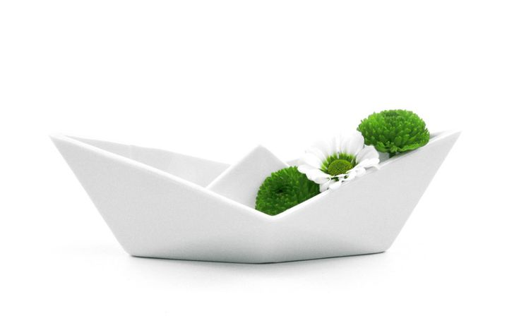 This porcelain is inspired by simple paper origami, which symbolizes playfulness and brings us back in time to our childhood.   It is made of porcelain, which helps to materialize the idea with cleanliness and elegance. The boat can be used for serving various sweets, candies and nuts, or for decorative purposes when filled with coffee beans for instance. Boats are stackable, and can form nice fractals decorating a table.