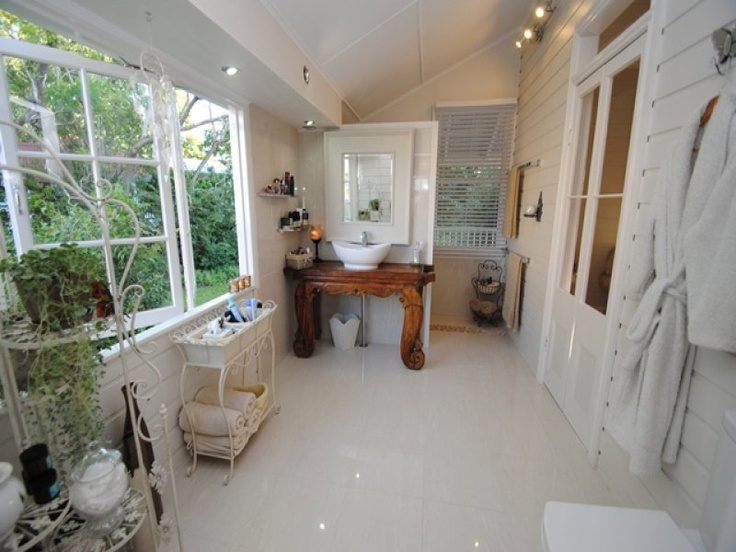 a 'queenslander' house ensuite on an enclosed verandah - note the french doors to the bedroom, and the pristine shiny white surface - juxtaposed against the fresh green of outside the window.