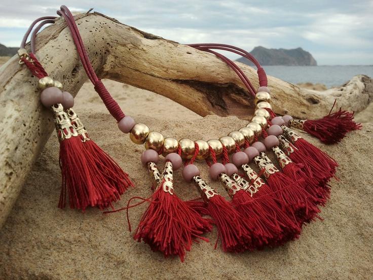 Maxi Collar Estilo Étnico, de MibolsoMivida.com. Cuerda de cuero rojo con abalorios en dorado y borlas de Nylon rojo engarzadas en canutillos de metal color oro.