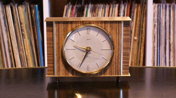 Eine sehr schöne, hochwertige Tischuhr aus den 60er Jahren. Hersteller war die Marke Exact. Sehr schöne klare und edle Formsprache. Das Gehäuse besteht aus Holz, lackiertem Teakfurnier und Messing. Kein Kunststoff! Die Uhr hat ein Gewicht von beinahe 1kg. Das Werk arbeitet elektro-mechanisch. Das bedeutet, dass die Uhr von einer Batterie in regelmäßgen Abständen automatisch aufgezogen wird, während das Werk selbst rein mechanisch arbeitet. Dadurch hat die Uhr selbstverständlich auch das…
