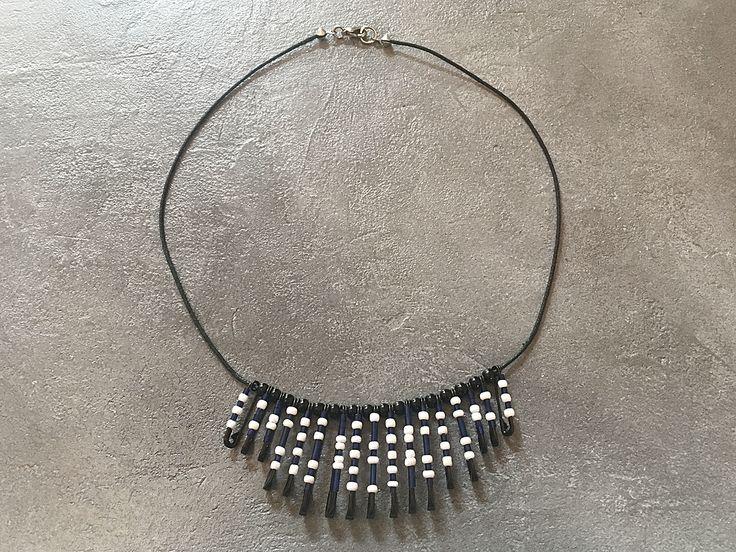 Mit dieser Perlenkette in blau, weiß und schwarz erhalten Sie ein Unikat. Sie wurde aus verschiedenen Glasstiften, Rocailles und Indianerperlen liebevoll handgefertigt. Einzigartig dürfte die Verwendung von Sicherheitsnadeln sein, was diese Perlenkette zu einem unverwechselbaren Designstück macht. Die Kette wird mit einem Karabinerverschluss geschlossen.