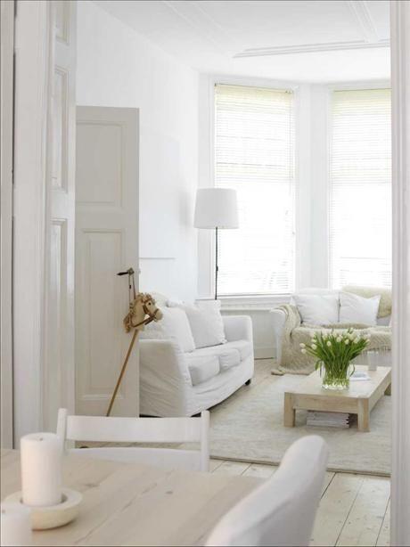 Vardagsrummet har en ombonad känsla med mjuka kuddar och plädar i olika vita nyanser. Bordet är egen...