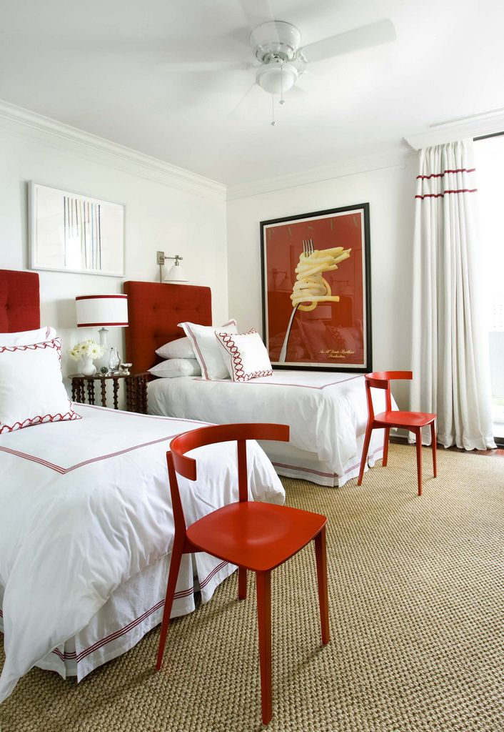 red double banding on white curtains, red upholstered headboard, chairs at end of bed, red and white bedroom