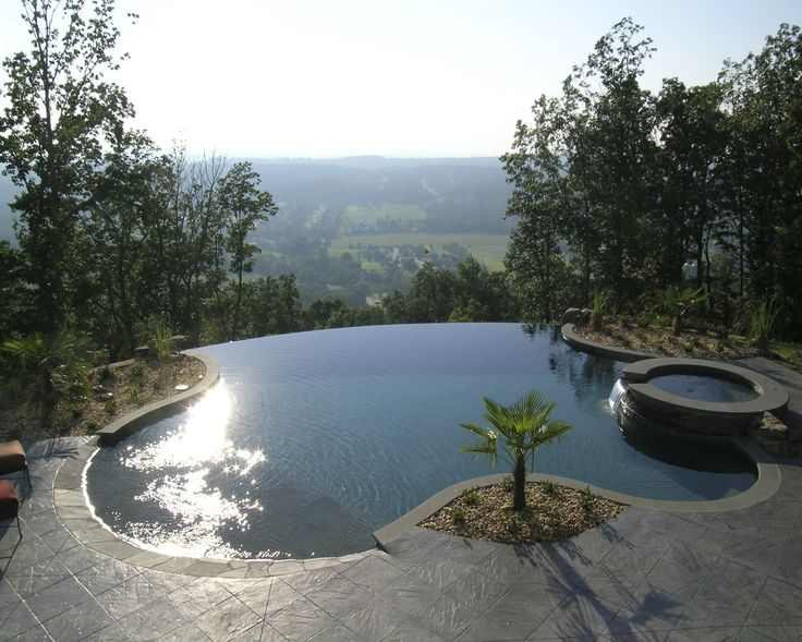 Negative Edge  swimming Pool and Spa in TN. Bluestone Coping and Stacked Stone on Spa. Stamped Pattern Concrete Deck. Tahoe Blue Pebble-Tec. My husband is building a negative edge pool with a view like this, right now. Gorgeous!