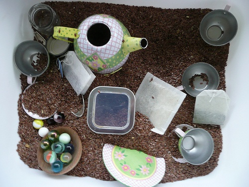 Tea Sensory Bin - How cute!  A tin tea set, flaxseed, real teabags and other fun stuff :)