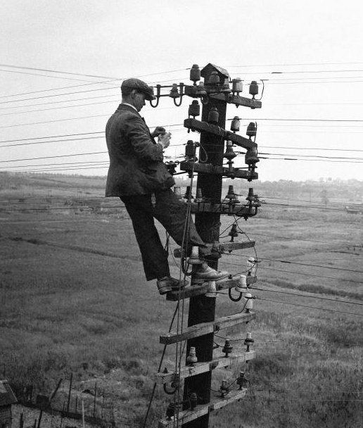 Lineman and insulators..........HOW IN THE WORLD IS HE STAYING UP THERE AND DRESSED IN A SUIT AT THAT.