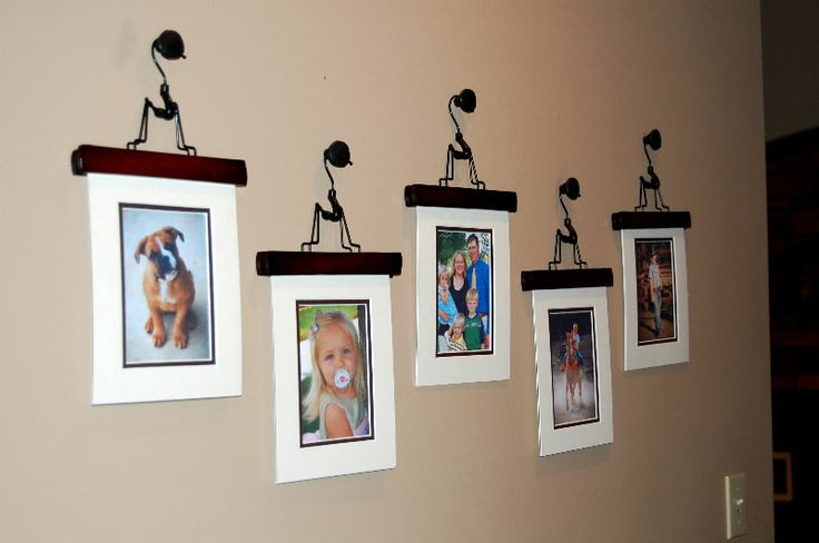 old door knobs holding wooden pant hangers used to hold photos...so clever