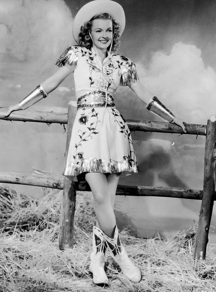 1945 | American actor and singer Dale Evans wearing a cow girl costume and leaning against a wooden fence. via @stylelist