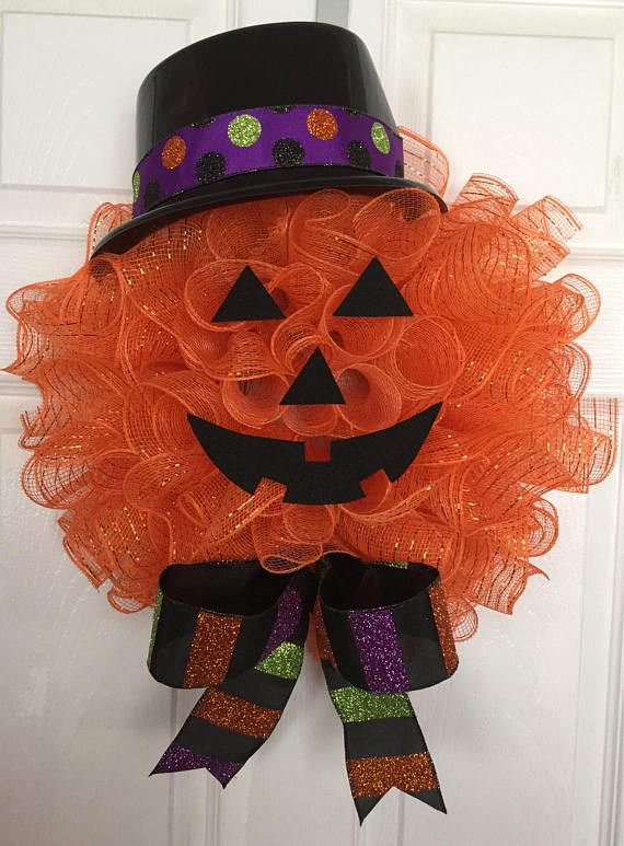 Handmade Halloween Deco Mesh Jack O Lantern Pumpkin Head Wreath Add a little sparkle to your door with this cute little guy! Sure to bring smiles to all your treat or treaters! This handmade wreath is made with a wire wreath, chenille stems, deco mesh, ribbon, plastic top hat, and felt. Deco Mesh is Orange. Ribbon includes: Multicolor polka dot and multicolor glitter stripes Top hat is plastic. Eyes/Nose/Mouth are made from felt. The wreath measures approx. 20 H x 17 W x 6 D. Free Shippi...