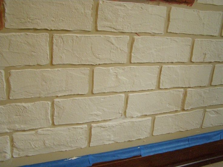 Make brick stencil,  cover with joint compound. Once dry faux paint brick to give a realistic look.