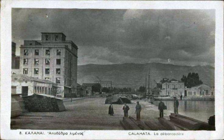 """Μια εικόνα της αποβάθρας του λιμανιού Καλαμάτας την περίοδο του Μεσοπολέμου.  Στο βάθος μοναδικό κτήριο το συγκρότημα Λιμεναρχείου - Τελωνείου, ενώ αριστερά δεσπόζει το κτήριο των μύλων """"Ευαγγελίστριας"""" και μακρύτερα διακρίνονται οι μύλοι """"Φεραδούρου - Αποστολάκη"""". Λίγα εμπορεύματα και ανάμεσα στους λιγοστούς ανθρώπους ο λιμενικός.      [Φωτό της Λίζας Κουτσαπλή από τη σελίδα στο fb """"Παλιές φωτογραφίες της Ελλάδας""""]"""