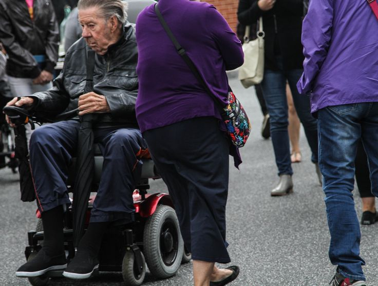 I really like that the two ladies are both wearing purple, and that their bodies break up the photo, makes it look like the man in the wheelchair wasn't coming into contact with them at all