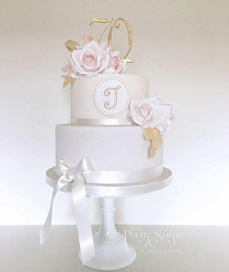 Two tier monogram 70th birthday cake in gold and blush pink