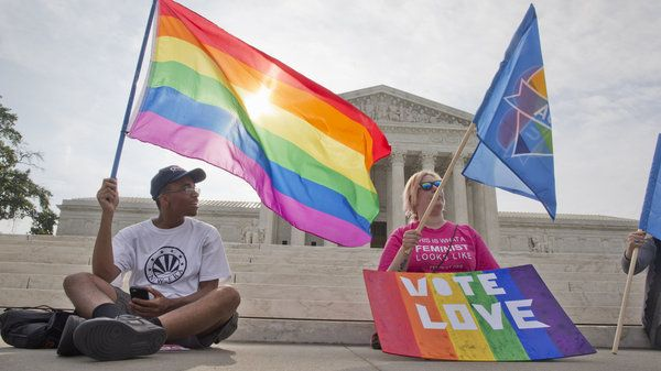 Carlos McKnight (left), and Katherine Nicole Struck hold flags in support of gay marriage outside of the Supreme Court on Friday.