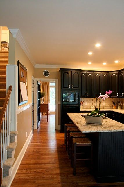 black cabinets with gorgeous island counter tops and cool back-splash with hard wood floors