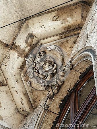 Stone man gargoyle on the building