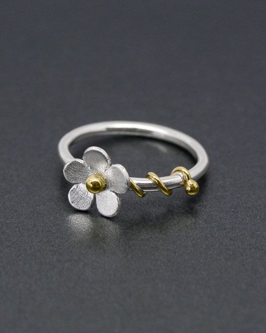 A charming daisy ring with a 10mm silver flower in a satin finish.  It has a brass bead to the centre and brass tendrils entwined around a silver wire band.  #brass #daisy #flower #handmade #ring #silver #starboardjewellery #jewellery #cornwall #uk #gb #westcountry #devon #england #silversmith #pretty #jeweller #jewellers #handmadejewellery