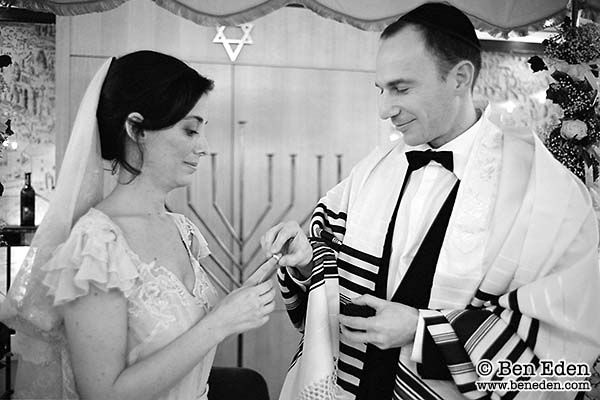 Groom places the wedding ring on bride's index finger