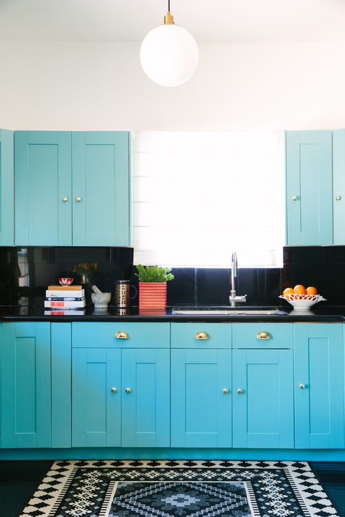 Turquoise kitchen cabinets with black backsplash and counters and black and white patterned floor