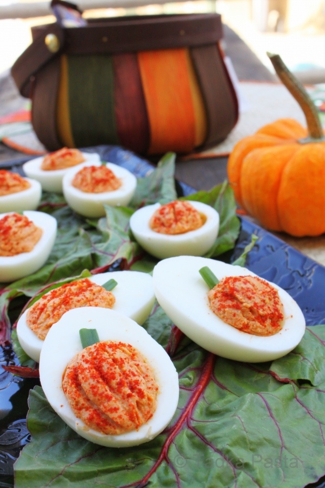 pumpkin deviled eggs..if you don't want these to have a curry taste, you could just make traditional deviled eggs and add orange food coloring..make lines with a toothpick and add a chive for a topper