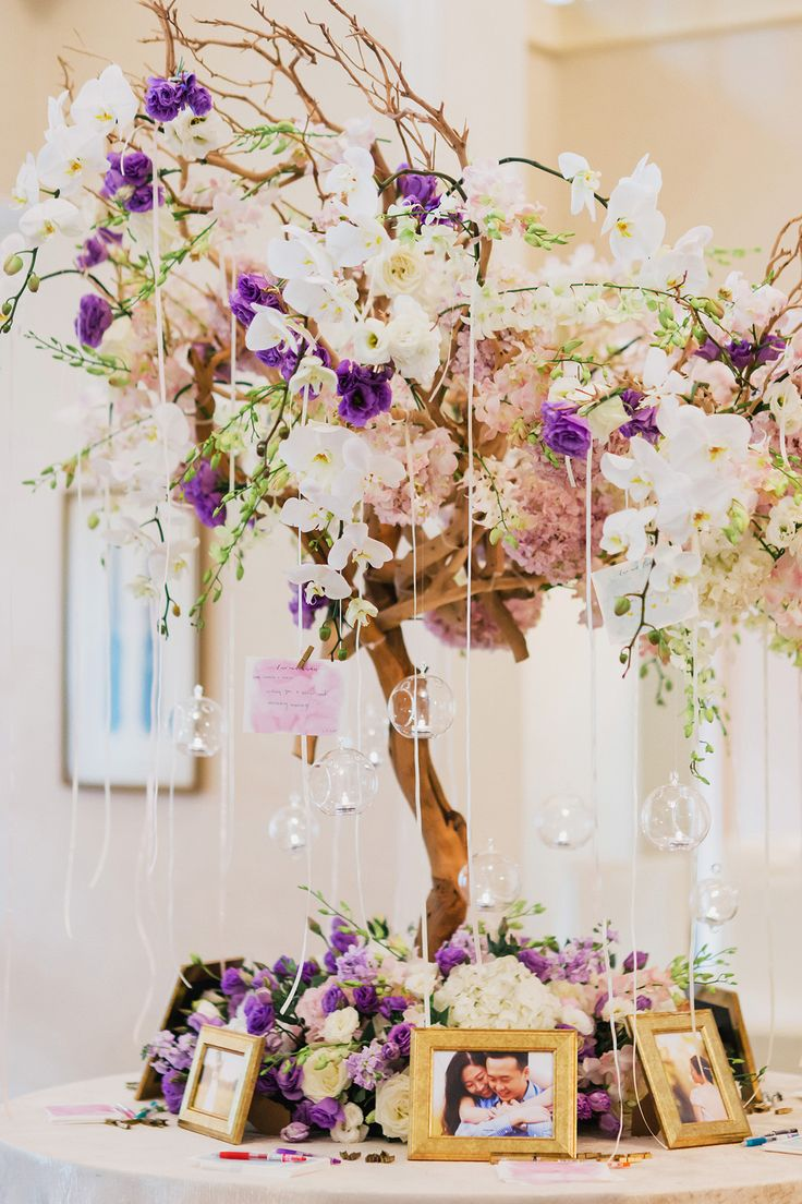 Ornate and lavish white and purple decor showcasing Terence and Chelsea's engagement photos in their wedding planned by Chere Weddings and Events