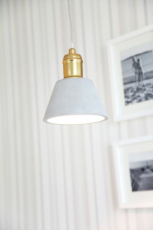 Fönsterlampa i betong med mässingsfärgade detaljer. H: 17 cm, Ø: 15 cm. E27 stor sockel max 40W(ingår ej). 3,5m transparent kabel med brytare och stickkontakt. <br><br>