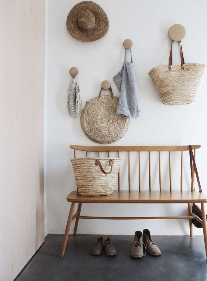 Ercol bench in hallway with polished concrete floor and beautiful modern baskets as decoration.